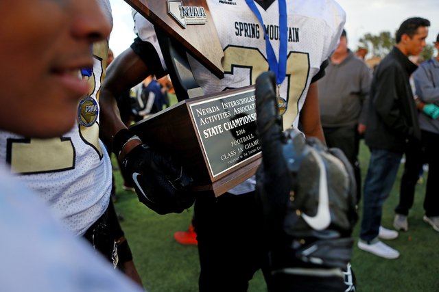 Spring Mountain Eagles hold their trophy after they winning the class 1A state football final neutral playoff game against Pahranagat Valley at Clark High School in Las Vegas, Saturday, Nov. 19, 2 ...