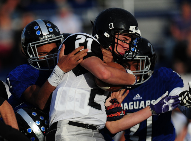 Desert Pines linebacker Marquise Lofton, left, wraps up Spring Creek running back Alex Woster in the second half of the NIAA Class 3A State championship game at Bishop Gorman High School in Las Ve ...
