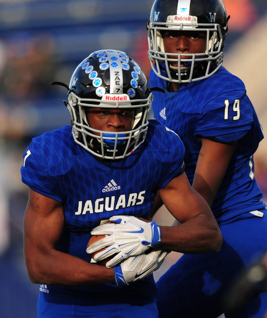 Desert Pines running back Isaiah Morris takes the handoff from quarterback Tyler Williamson (19)against Spring Creek in the second half of the NIAA Class 3A State championship game at Bishop Gorma ...