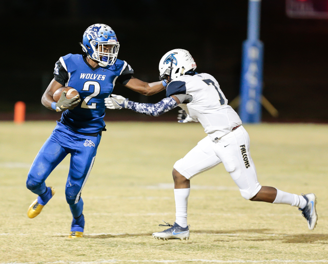 Basic senior De'Shawn Eagles (2) attempts to push off on Foothill senior Blake High (7) while moving up the field during  the Sunrise Region semifinal football game held at Basic High School in He ...
