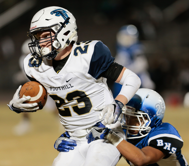 Foothill senior Brandon Hargis (23) attempts to move the ball down the field, as Basic junior Jordan Gallegos (25) hangs on during  the Sunrise Region semifinal football game held at Basic High Sc ...