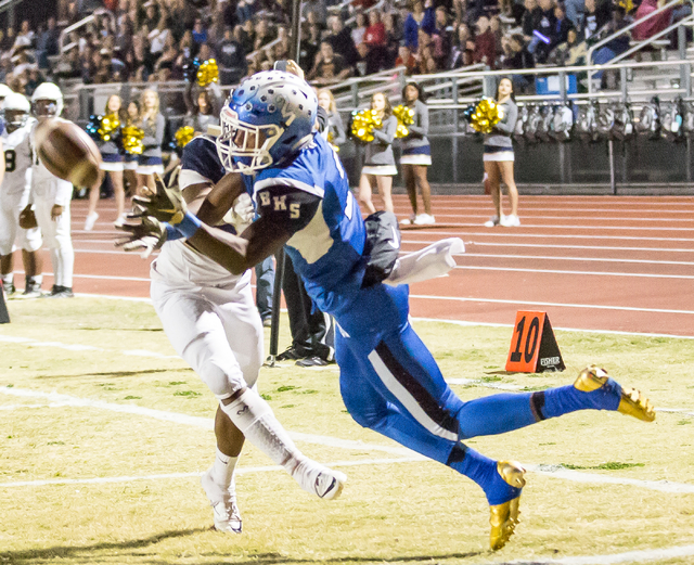Foothill junior Titus Lowe (25) makes an attempt to stop  Basic senior De'Shawn Eagles (2) from catching a ball  during  the Sunrise Region semifinal football game held at Basic High School in Hen ...