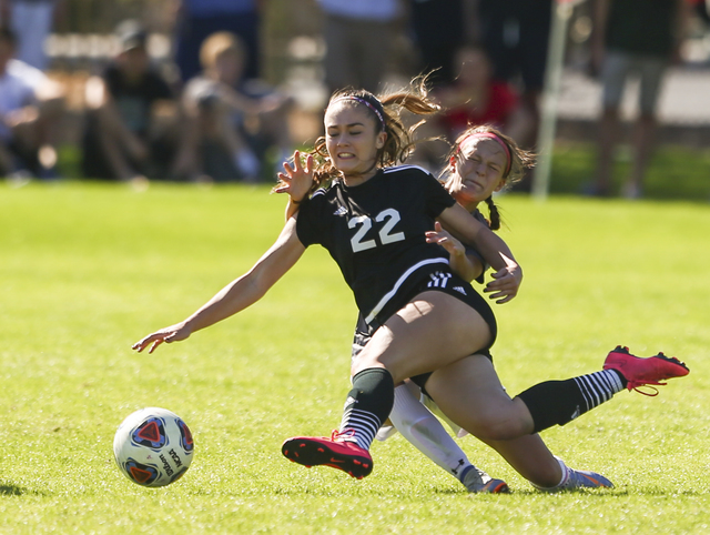 Palo Verde's Sloan Nelson (22) kicks the ball while colliding with an unidentified Arbor View player during the Sunset Region girls soccer championship game at Bettye Wilson Soccer Complex in Las  ...