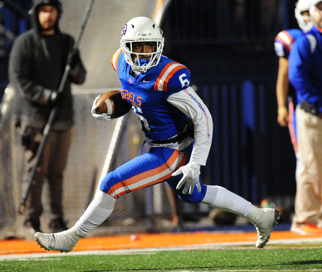 Bishop Gorman safety Austin Arnold looks for running room after catching a flea-flicker pass for a first down against Faith Lutheran in the first half of their prep football game at Bishop Gorman  ...
