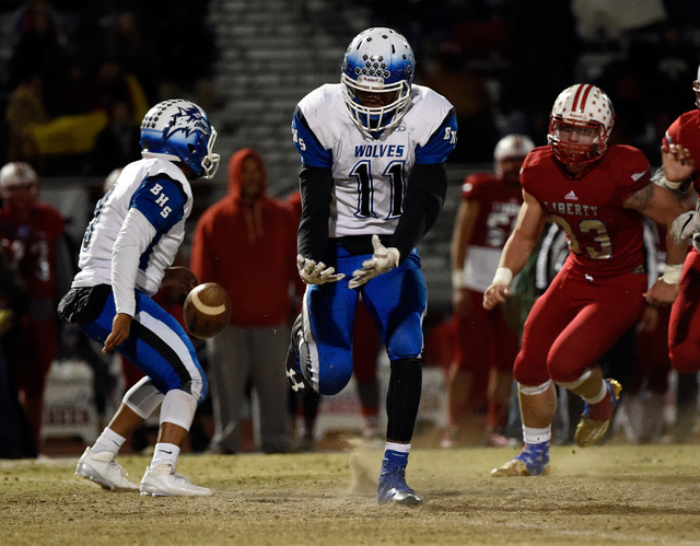 Basic's Frank Harris (11) drops the ball after a hand off by quarterback Aaron McAllister during a high school football game against Liberty at Liberty High School Friday, Nov. 18, 2016, in Hender ...
