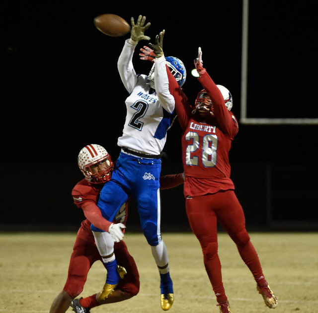 Basic's De'Shawn Eagles (2) attempts to catch the ball against Liberty's Austin Fiaseu and Dominique Turner (28) during a high school football game at Liberty High School Friday, Nov. 18, 2016, in ...