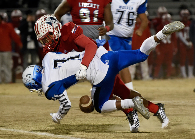 Basic's Dorian McAllister (7) drops the ball after being hit by Liberty's Austin Fiaseu during a high school football game at Liberty High School Friday, Nov. 18, 2016, in Henderson. David Becker/ ...