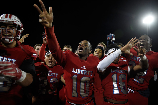 Liberty's Terris Hamilton (10) celebrates with teammates their 58-14 victory over Basic to win the Sunrise Regional championship after a high school football game at Liberty High School Friday, No ...
