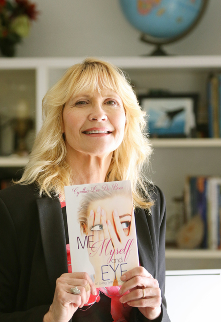 "Cynthia De Boer, author of ""Me, Myself & Eye,"" shows her book, Wednesday, Oct. 12, 2016, in Henderson. De Boer lost her left eye due to a series of events resulting in retinal detachment. Rond ..."