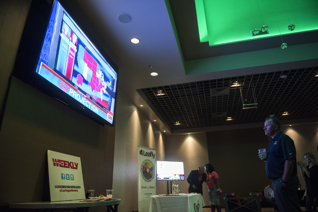 People watch as early election results are displayed on TV during the Las Vegas Weekly's Question 2 watch party inside the Sake Rok restaurant in Las Vegas on Tuesday, Nov. 8, 2016. Martin S. Fuen ...