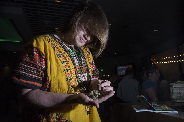 Pro marijuana supporter Justin Gwinn looks at his strain of marijuana during the Las Vegas Weekly's Question 2 watch party inside the Sake Rok restaurant in Las Vegas on Tuesday, Nov. 8, 2016. (Ma ...