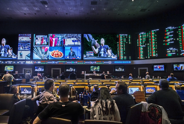 Customers watch an interview with Oakland Raiders quarterback Derek Carr at The Race & Sports Book at Green Valley Ranch on Monday, Nov. 14, 2016, in Henderson. (Benjamin Hager/Las Vegas Revie ...