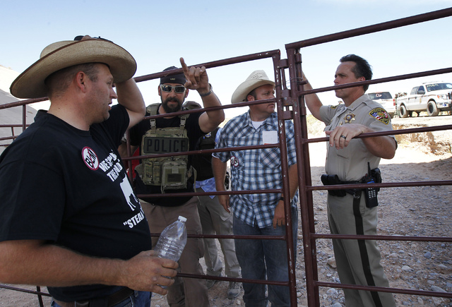 Dave Bundy, middle, and his brother Ammon Bundy, left, talk with Las Vegas police Chief Deputy Tom Roberts, right, while trying to persuade the BLM to release their impounded cattle outside of Bun ...