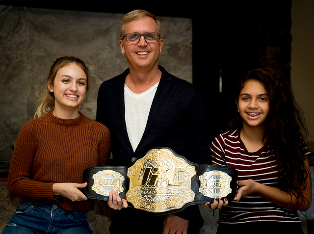 Michael Mossholder, UFC executive vice president of the Global Sales Division with his daughters, left, Marissa and Ariana, in his luxury Summerlin home showing off a championship belt. (Tonya Harvey)