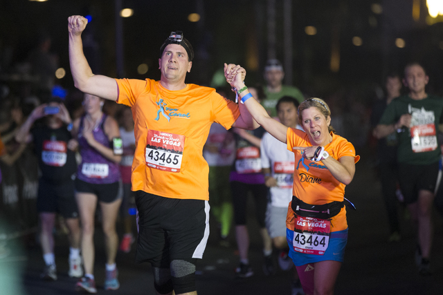 Matthew Olsen, left, and Diane Olsen complete the 10K run in the annual Rock 'n' Roll Marathon at the Strip near The Mirage hotel-casino on Sunday, Nov. 13, 2016, in Las Vegas. Erik  ...
