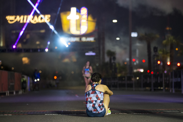 Katja Goldring sits on the ground at the finish line after running the half-marathon in the annual Rock 'n' Roll Marathon at the Strip near The Mirage hotel-casino on Sunday, Nov. 13 ...