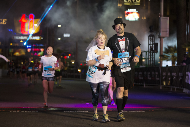 Teresa Moore-Millslagel, left, and Michael Millslagel complete the half-marathon run in the annual Rock 'n' Roll Marathon at the Strip near The Mirage hotel-casino on Sunday, Nov. 13 ...