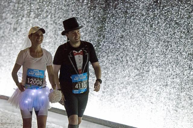 Runners Fabio Viebrantz and Caroline Viebrantz of Brazil head to Rock 'n' Roll Marathon's  Ҳun-thruӠweddings at The Park in Las Vegas, Sunday, Nov. 13, 2016. More than 200 couples part ...
