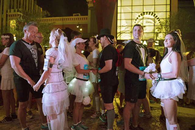 "Melanie Correia, right, and Stanley Dymbecki, second from right, of Toronto, Canada, wait to be married during the Rock 'n' Roll Marathon's  ""run-thru"" weddings at The Park in Las Ve ..."