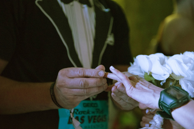 "Stanley Dymbecki, left, places a ring on Melanie Correia's finger as they're married during the Rock 'n' Roll Marathon's ""run-thru"" weddings at The Park in Las Vegas, Sunday, Nov. 13 ..."