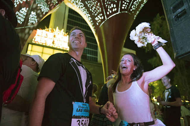 "Melanie Correia, right, and Stanley Dymbecki, of Toronto, Canada, are married during the Rock 'n' Roll Marathon's ""run-thru"" weddings at The Park in Las Vegas, Sunday, Nov. 13, 2016. ..."