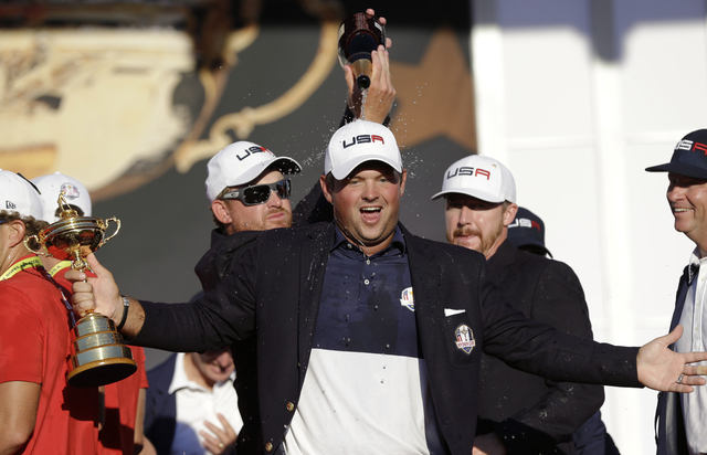 United States' Jimmy Walker and United States' Ryan Moore pour champagne on United States' Patrick Reed during the closing ceremony of the Ryder Cup golf tournament Sunday, Oct. 2, 2016, at  ...