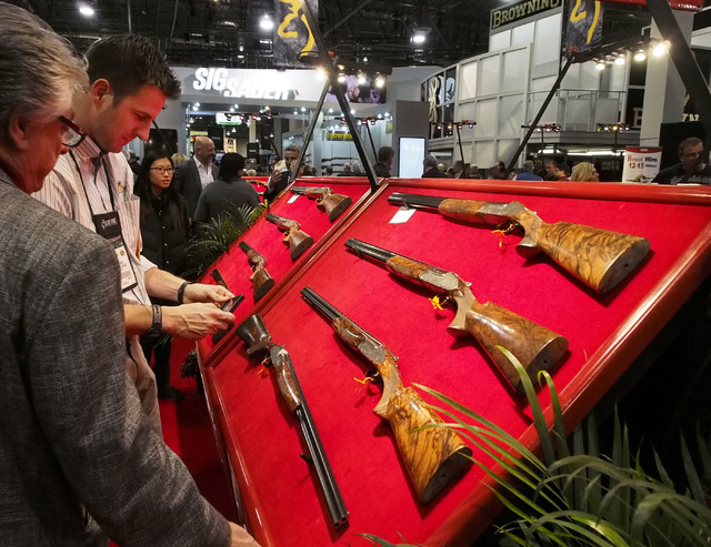 Brian Kock, of Cleveland, Ohio, second from left, takes a photo of a matched set of over/under shotguns at the Perazzi booth at the 2014 Show Show at the Sands Expo in Las Vegas, Tuesday, Jan. 14, ...