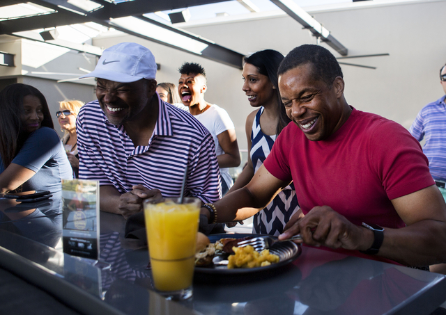 """Soul Train Producer Tony Cornelius, right, eats a plate of soul food made by Chef Huda at Topgolf Las Vegas for the """"Soul Lunch & Greens,"""" a benefit for the Don Cornelius Foundation Friday, No ..."""