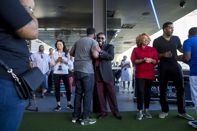 """Singer Edward """"Eddie"""" Levert, center right, and Shawn Stockman, member of the Boyz II Men rhythm-and-blues group hug at Topgolf Las Vegas for the """"Soul Lunch & Greens,"""" a benefit for the Don C ..."""