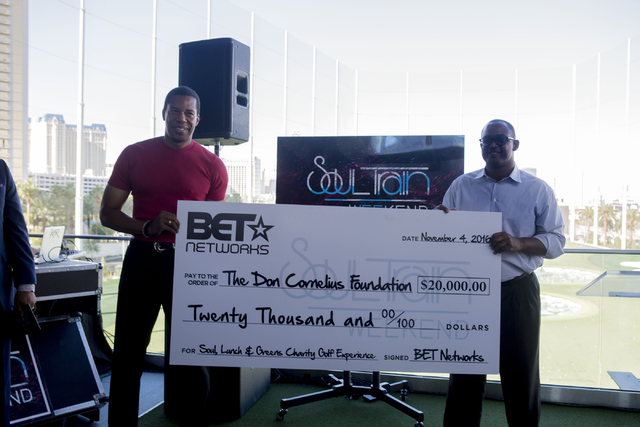 """Richard Gay, executive vice president of BET Networks, right, presents Tony Cornelius, Soul Train producer, left, a 20,000 dollar check at Topgolf Las Vegas for the """"Soul Lunch & Greens,"""" a be ..."""