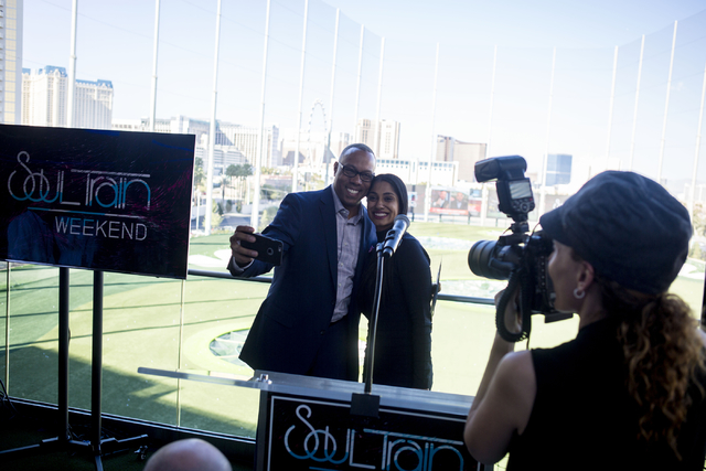 """ESPN anchor Jay Harris, left, and Seema Sadekar, professional golfer, get their photo taken at Topgolf Las Vegas for the """"Soul Lunch & Greens,"""" a benefit for the Don Cornelius Foundation Frida ..."""