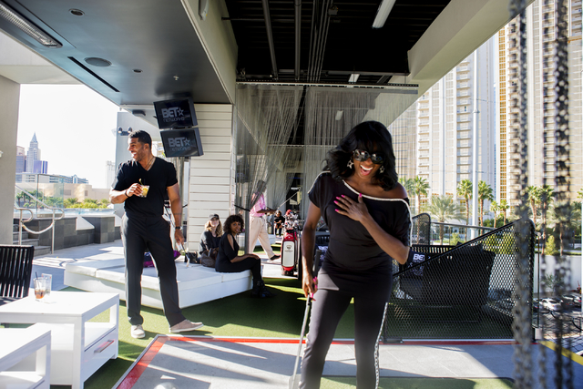 """Jimmy Jackson, broadcaster for Fox Sports 1 in LA and former NBA player, left, and Jin Jin Reeves, performer on Hitzville, laugh while hitting golf balls at Topgolf Las Vegas for the """"Soul Lunch & ..."""