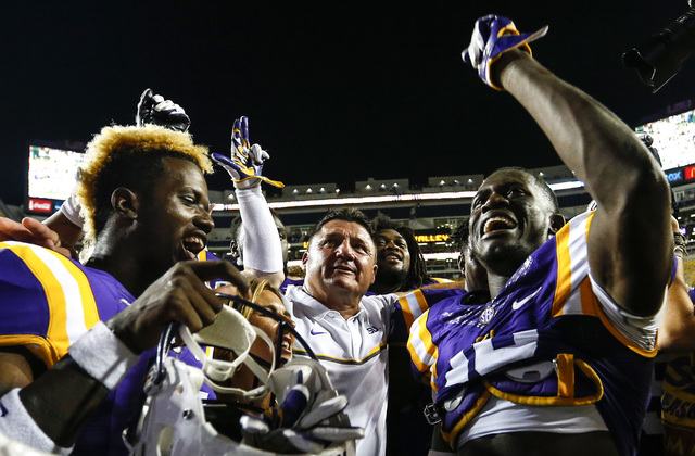 LSU wide receiver Malachi Dupre (15), coach Ed Orgeron, and cornerback Tre'Davious White (18) sing the alma mater after an NCAA college football game, Saturday, Oct. 15, 2016, in Baton Rouge, La.  ...