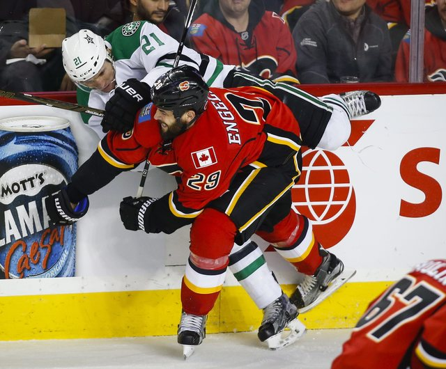 Dallas Stars' Antoine Roussel, left, from France, is checked by Calgary Flames' Deryk Engelland, during the first period of an NHL hockey game Thursday, Nov. 10, 2016, in Calgary, Alberta. (Jeff M ...