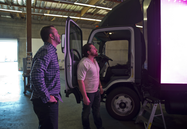 Managing partners of Kre8 Media Outdoor Advertising Shaun Habibian, right, and Jeremie Watkins watch one of their mobile digital billboards inside their shop near the Palms hotel-casino on Friday, ...