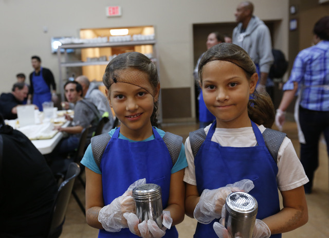 Volunteers Ava Meeks, 8, left, and her twin sister Leah, 8, bring salt and pepper to the table while other volunteers serving turkey dinners to the guests at the Las Vegas Rescue Mission in Las Ve ...