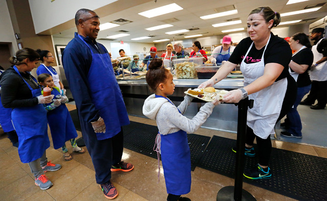 Volunteer Megan Swartz, right, passes a plate to volunteer Jaya Smith , 7, of Las Vegas, center, while serving turkey dinners to the guests at the Las Vegas Rescue Mission in Las Vegas, Wednesday, ...