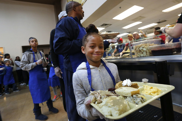 Volunteer Jaya Smith , 7, of Las Vegas helps  serve turkey dinner to the guests with her grandfather Robert Smith, behind, at the Las Vegas Rescue Mission in Las Vegas, Wednesday, Nov. 23, 2016. C ...