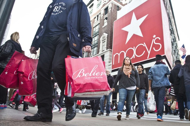 Shoppers carry bags as they cross a pedestrian walkway near Macy's in Herald Square in New York in this file photo. (Bebeto Matthews/AP)
