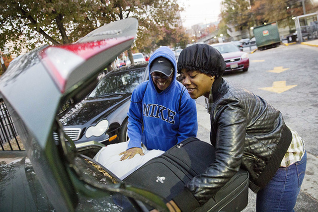 April Traylor, of Nashville, Tennessee, left, is helped by her daughter Latisha Brown after arriving on a bus to spend the Thanksgiving holiday in Atlanta. Almost 49 million people are expected to ...