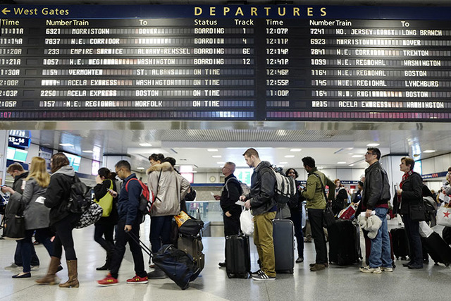 Passengers stand beneath an electronic signboard in New York's Penn Station as they wait to board a train, Sunday, Nov. 27, 2016. (AP Photo/Mark Lennihan)
