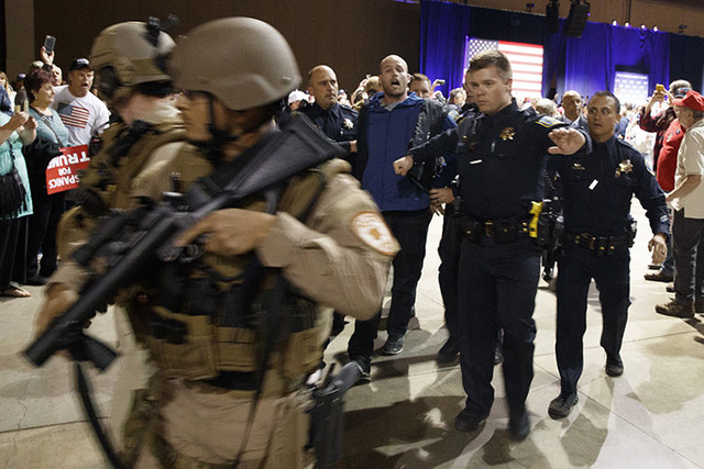 A man is escorted by law enforcement officers moments after Donald Trump was rushed offstage by Secret Service agents during a campaign rally in Reno, Nev., on Saturday, Nov. 5, 2016. (Evan Vucci/ ...