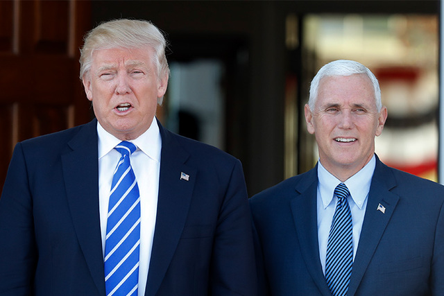 President-elect Donald Trump and Vice President-elect Mike Pence pause for photographs as they arrive at the Trump National Golf Club Bedminster clubhouse in this file photo. (Carolyn Kaster/AP)