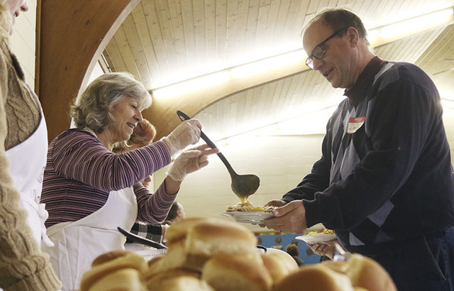 Cheryl Plankey of West Bend smiles as she adds gravy to the plate of Dan Walk of Germantown during the community Thanksgiving Day meal Thursday, Nov. 24, 2016 at Faith Lutheran Church in Germantow ...