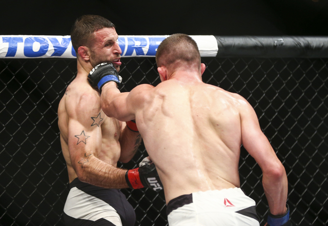 Tarec Saffiedine, left, takes a punch from Rick Story, right,in their welterweight bout during UFC Fight Night 88 at Mandalay Bay Events Center in Las Vegas on Sunday, May 29, 2016. (Chase Stevens ...