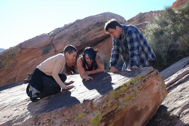 During a Feb. 7 research trip to the Gold Butte area northeast of Las Vegas, UNLV undergraduate students, from left, Stephanie Vosburgh, Summer Matz and Cameron Rickerson examine the fossilized tr ...