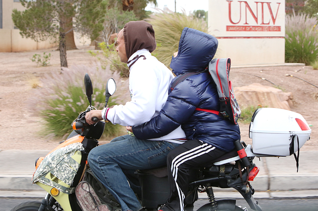 Riders bundled up as they ride their moped on Tropicana Avenue during a cold and rainy morning. (Bizuayehu Tesfaye/Las Vegas Review-Journal) Follow @bizutesfaye