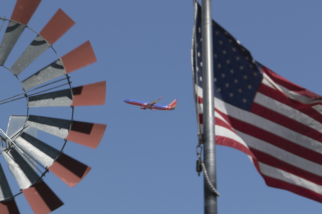 A plane taking off from McCarran International Airport is flanked by a windmill and an American flag blowing in the wind at the Western Trails Neighborhood Park in Las Vegas. (Richard Brian/Las Ve ...