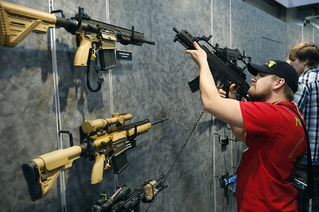 In this Jan. 19, 2016 file photo, Nolan Hammer looks at a gun at the Heckler & Koch booth at the Shooting, Hunting and Outdoor Trade Show in Las Vegas.  (AP Photo/John Locher, File)