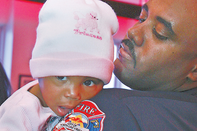 Capt. Yaphet Miller, 43, is shown during a reunion with then 11-month-old Jaielayah Swindell in January 2007. Miller had rescued the baby from a fire a few weeks earlier. The North Las Vegas fire  ...